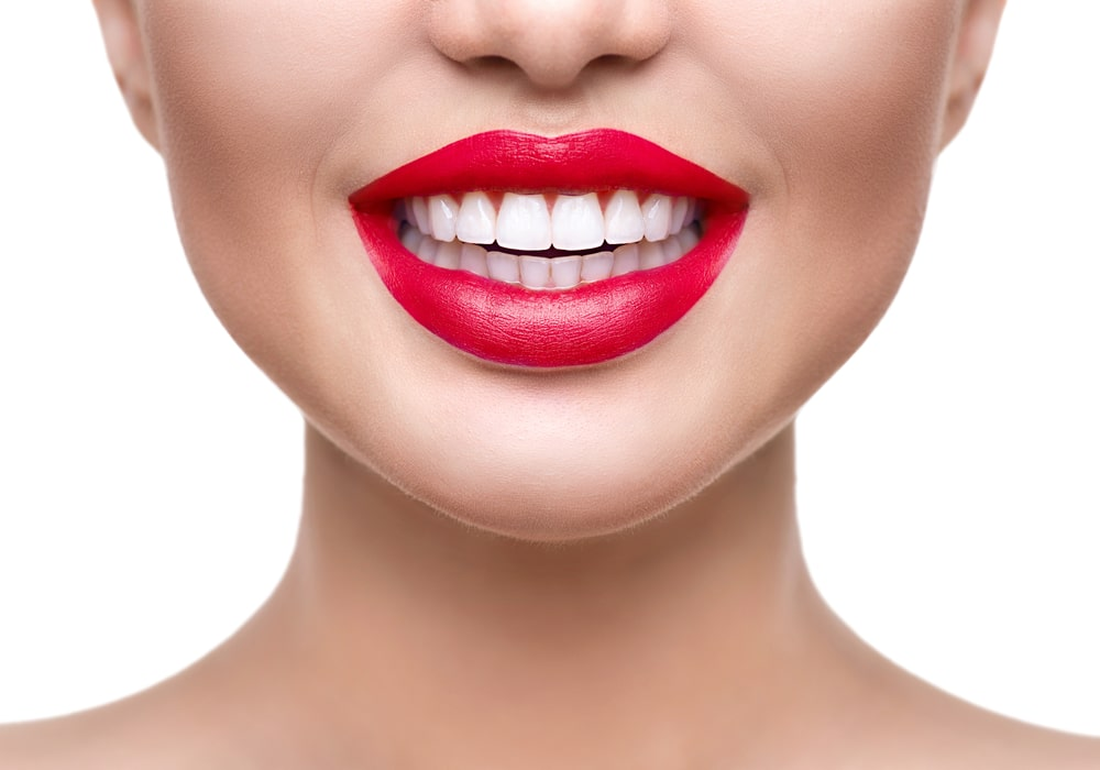 eeth whitening. Healthy white smile closeup. Beautiful girl with red lips isolated on white